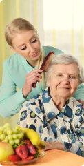 caregiver combing old woman's hair