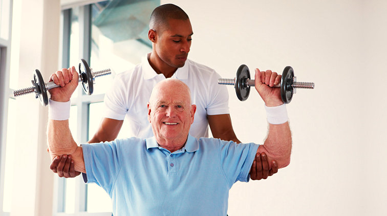 man assisting old man to exercise