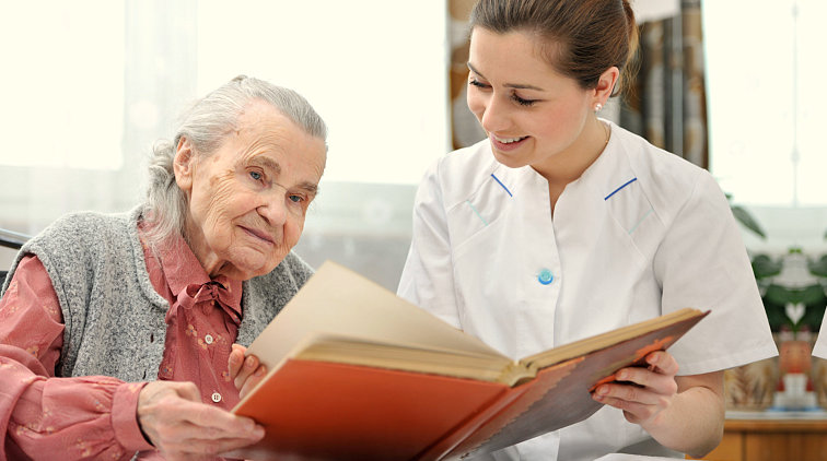 nurse and old woman reading a book
