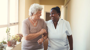 old woman and caregiver smiling at each other