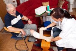 caregiver dressing an elderly man wound